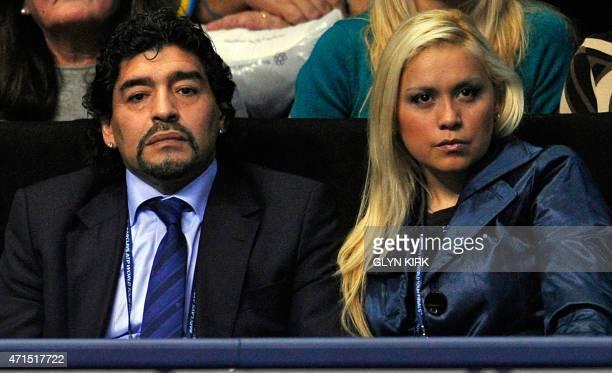 Former Argentina football coach Diego Maradona and Veronica Ojeda watch as Serbia's Novak Djokovic plays Czech Republic player Tomas Berdych during...