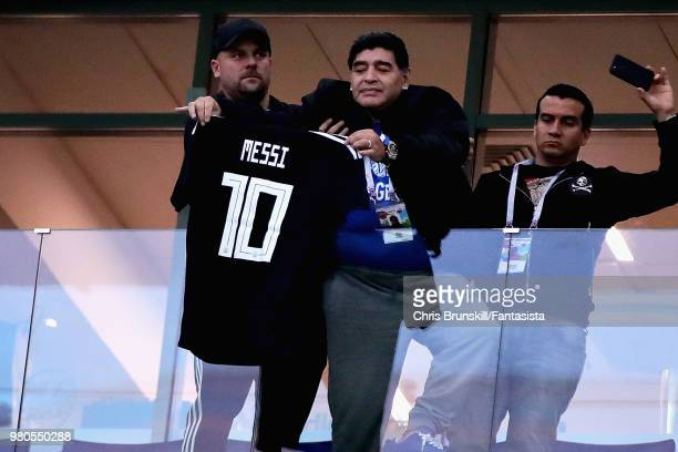 Former Argentina player Diego Maradona holds a tribute shirt for Lionel Messi of Argentina before the 2018 FIFA World Cup Russia group D match...