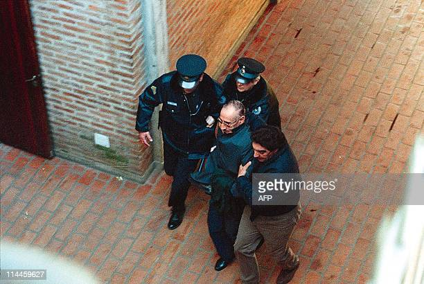 Former Argentine dictator Jorge Videla is escorted by police into the San Isidro court building in Buenos Aires 11 June. Videla, who was arrested 09...
