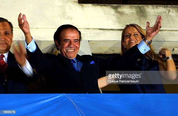 Former Argentine President Carlos Menem accompanied by his wife Cecilia Bolocco and his Vice Presidential candidate Romero Salutes greets supporters...