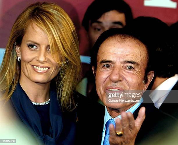 Former Argentine President Carlos Menem accompanied by his wife Cecilia Bolocco greets supporters at a media conference in his headquarters after...