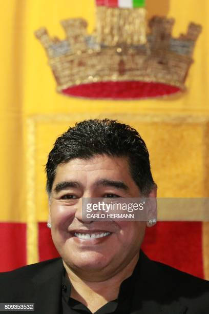 Former Argentinian football player Diego Armando Maradona smiles as he receives the honorary citizenship of Naples from city's mayor during a...