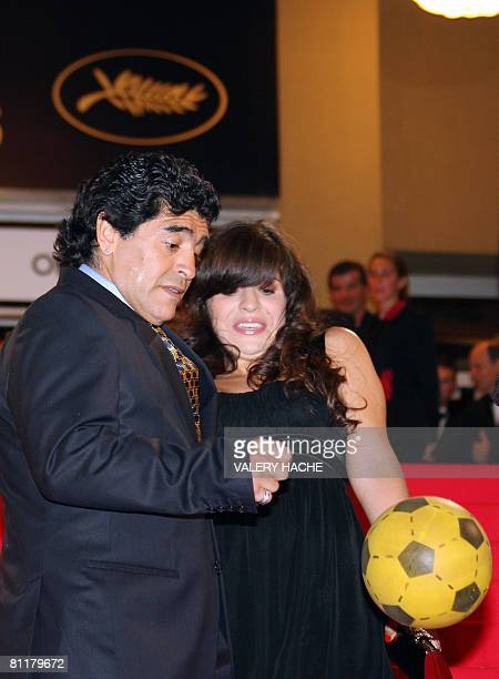 Former Argentinian football player Diego Maradona dribbles next to his daughter Giannina as he arrives to attend the screening of Serbian director...