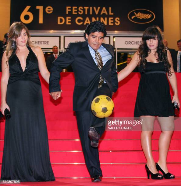 Former Argentinian football player Diego Maradona dribbles with a ball as he arrives with his daughters Dalma and Giannina to attend the screening of...