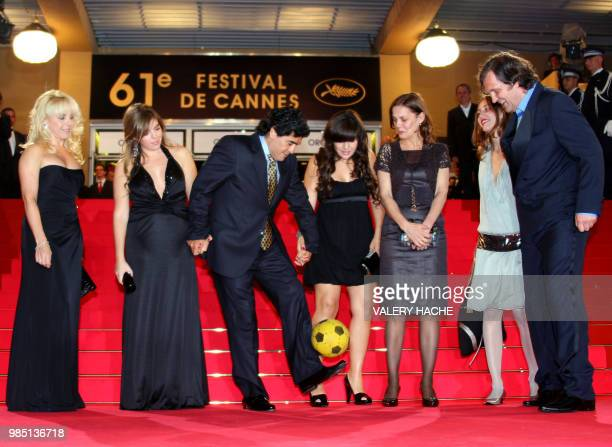 Former Argentinian football player Diego Maradona dribbles with a ball as he arrives with his wife Claudia daughters Dalma and Giannina Serbian...