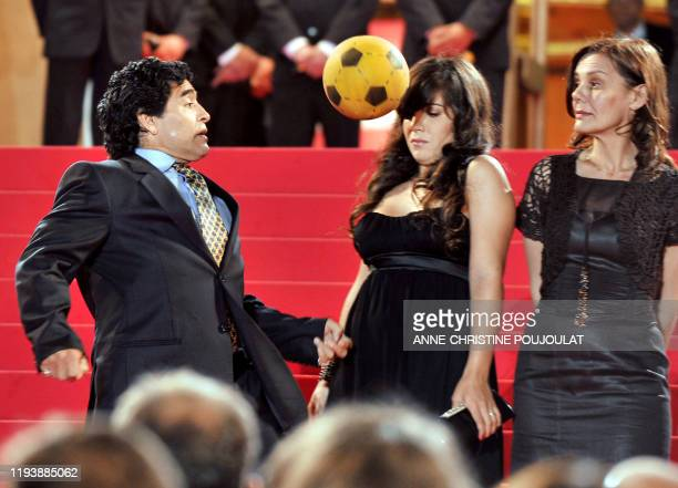 Former Argentinian football player Diego Maradona dribbles with a ball next to his daughter Giannina and Serbian producer Maja Kusturica as he...