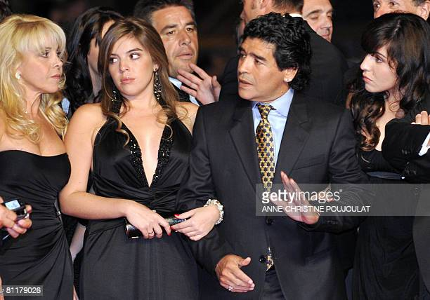 Former Argentinian football player Diego Maradona gestures as he arrive with his wife Claudia and daughters Dalma and Giannina to attend the...
