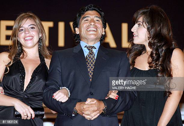 Former Argentinian football player Diego Maradona smiles as poses with his daughters Dalma and Giannina upon arriving to attend the screening of...