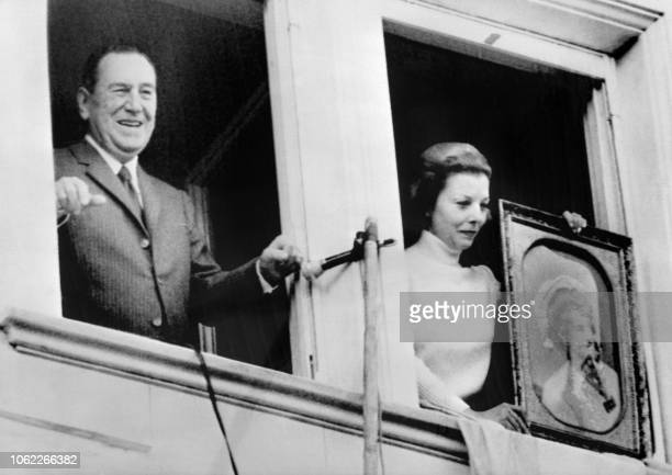 Former Argentinian president Juan Peron waves to the crowd while his wife Isabel Peron is presenting a portrait of Evita Peron from the balcony of...