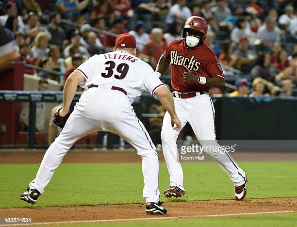 Former Arizona Diamondbacks player Orlando Hudson is blocked from scoring by Mike Fedders during an alumni game at Chase Field on August 9 2015 in...