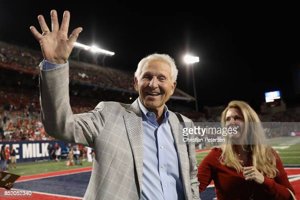 Former Arizona Wildcats basketball coach Lute Olson waves to fans as he walks with wife Kelly Pugnea during the first half of the college football...