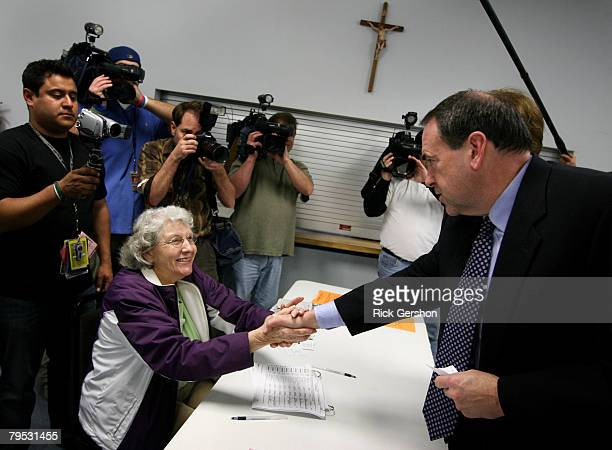 Former Arkansas Governor and Republican presidential hopeful Mike Huckabee greets election commission employee Marjorie Kelly as he and his wife...