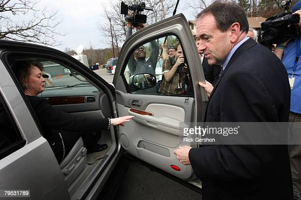Former Arkansas Governor and Republican presidential hopeful Mike Huckabee helps his wife Janet into their car after they cast their ballots for the...