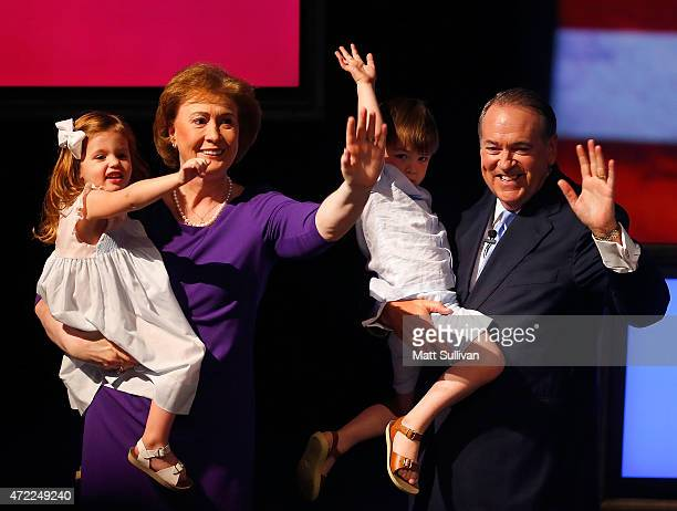 Former Arkansas Governor Mike Huckabee and his wife Janet hold their grandchildren Scarlet Sanders and Chandler Huckabee after announcing his...