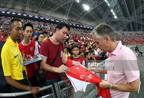 Former Arsenal legend Alan Smith signs autographs for fans during the Arsenal FC open training session ahead of the match between Arsenal and...