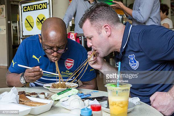 Former Arsenal player Ian Wright and former Everton player Graham Stuart eat noodles at a breakfast with bloggers at Tiong Bahru market during day 2...