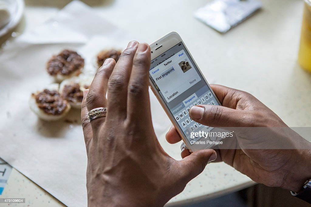 Former Arsenal player Ian Wright tweets about his food at a breakfast with bloggers at Tiong Bahru market during day 2 of the Barclays Asia Trophy Ticket Launch 2015 on May 13, 2015 in Singapore.