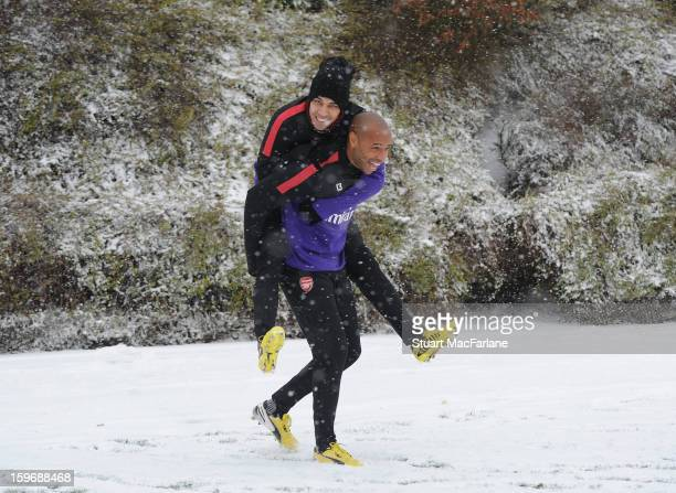 Former Arsenal player Thierry Henry laughs with Andre Santos of Arsenal before a training session at London Colney on January 18, 2013 in St Albans,...