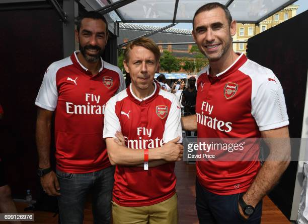 Former Arsenal players Robert Pires and Martin Keown pose with DJ Gilles Peterson on stage to help introduce the new Arsenal Puma Home kit at King's...