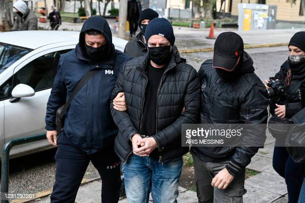 Former artistic director of Greece's national theatre Dimitris Lignadis is escorted handcuffed by police officers to the examining magistrate in...
