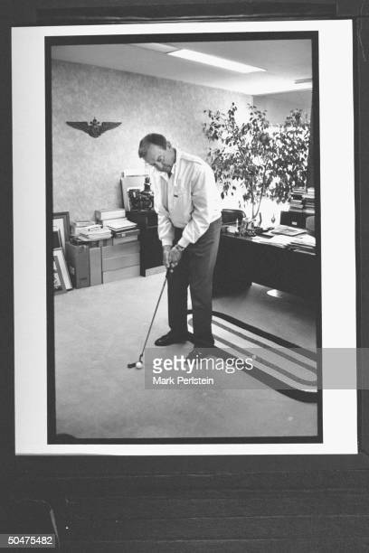 Former astronaut Alan Shepard Jr poised w golf club as he practices putting in the office of his business development firm during the 1971 Apollo 14...