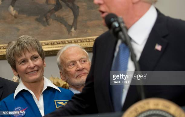 Former Astronaut Buzz Aldrin alongside NASA Astronaut Peggy Whitson listens as US President Donald Trump speaks during a signing ceremony for Space...