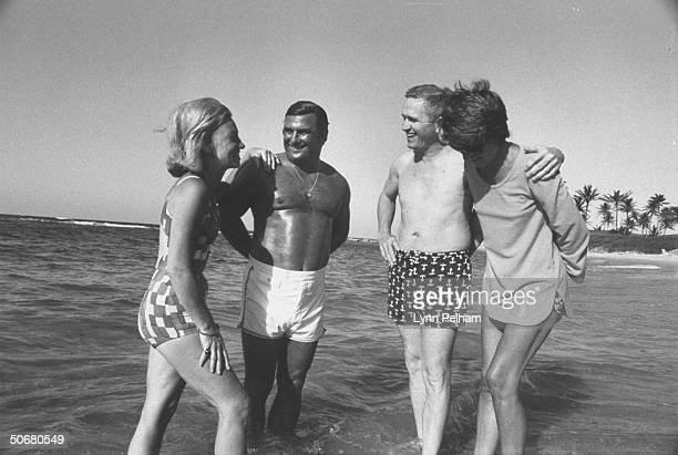 Former astronaut Frank Borman vice president of Eastern Airlines standing with his wife and football coach Hank Stram and his wife at the beach