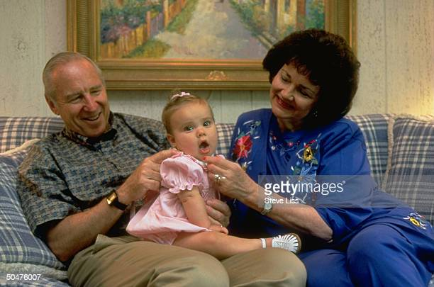 Former astronaut Jim Lovell wife Marilyn cuddling w granddaughter Emily on sofa at their summer home