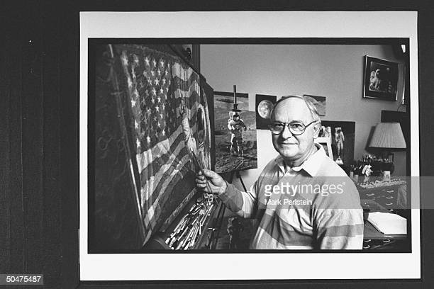 Former astronaut turned artist Alan Bean holding paint brush up to his painting America's Team Just the Beginning as he poses nr a few of his other...