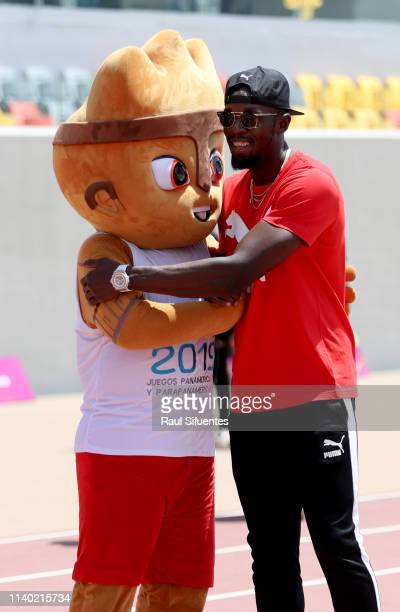 Former athlete Usain Bolt hugs Milco official Pan American Games mascot for Lima 2019 during the inauguration of the new track of Villa Deportiva...