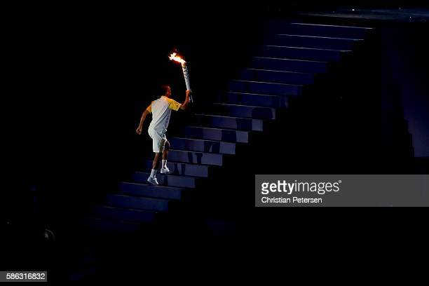 Former athlete Vanderlei de Lima lights carries the Olympic Torch during the Opening Ceremony of the Rio 2016 Olympic Games at Maracana Stadium on...