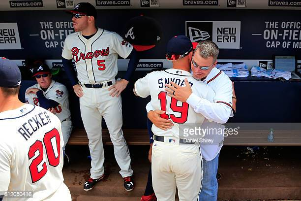 Former Atlanta Braves player Chipper Jones hugs Brandon Snyder of the Atlanta Braves in the dugout prior to the game at Turner Field on October 2...
