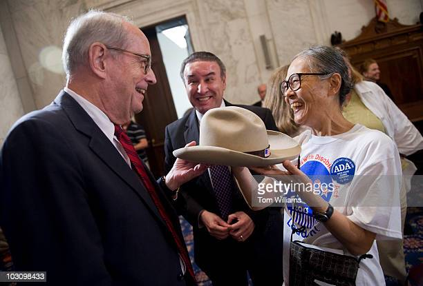 Former Attorney General Dick Thornburgh left gives back a cowboy worn by the late Justin Dart to his widow Yoshiko Dart as Ralph Neas president and...