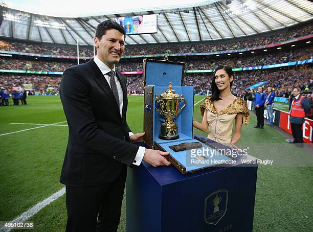Former Australia player John Eales poses with the Webb Ellis Cup with actress Tao Okamoto prior to the 2015 Rugby World Cup Final match between New...