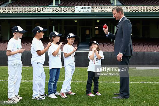 Former Australian cricketer Brett Lee shows young players how to hold a ball when bowling during the announcement of the NSW venues for the 2015 ICC...
