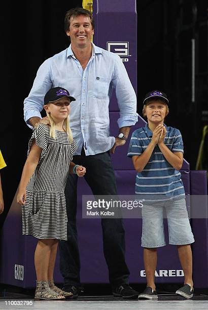 Former Australian cricketer Glenn McGrath and his children Holly and James take part in the three quarter time activities on court during the round...