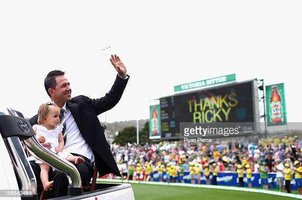 Former Australian cricketer Ricky Ponting waves to the crowd on a farewell lap with his daughter Matisse during day one of the First Test match...