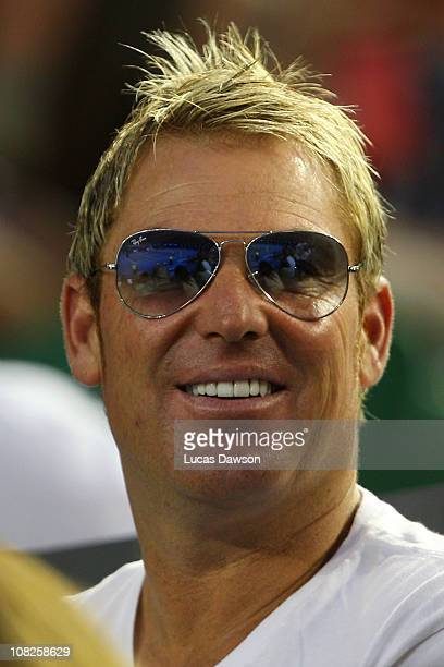 Former Australian cricketer Shane Warne watches the fourth round match between Andy Roddick of the United States of America and Stanislas Wawrinka of...