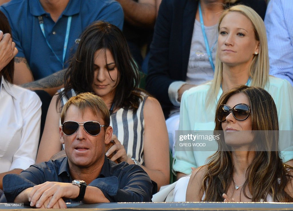 Former Australian international cricketer Shane Warne (L) and British actress Elizabeth Hurley look on as Switzerland's Roger Federer takes part in his men's singles match against Australia's Bernard Tomic on the sixth day of the Australian Open tennis tournament in Melbourne on January 19, 2013.