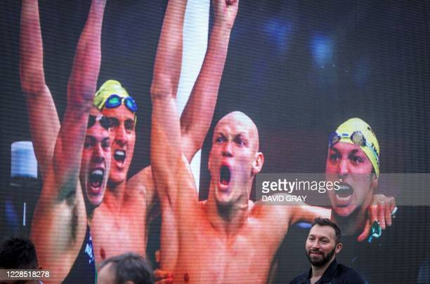 Former Australian Olympian Ian Thorpe reacts as he stands in front of a screen showing a photograph of him winning with teammates in the 4x100m...
