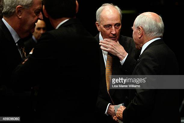 Former Australian Prime Ministers Paul Keating and John Howard shake hands prior to German Chancellor Angela Merkel taking to the stage for the...