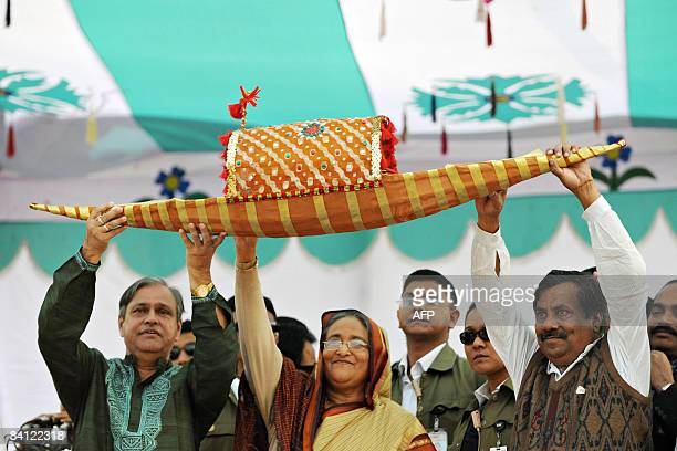 Former Bangladeshi prime minister and chief of the Awami League party Sheikh Hasina Wajed holds up the party symbol of a boat with other officials...