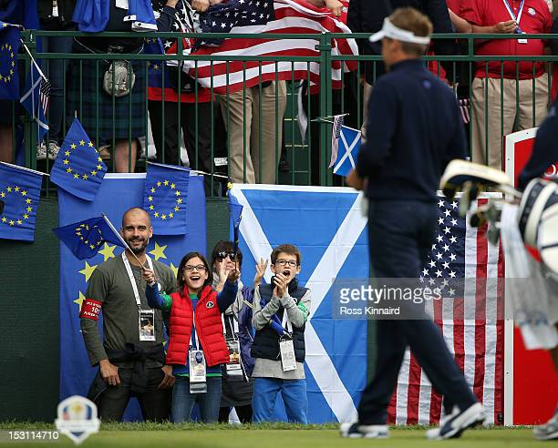 Former Barcelona football team manager Pep Guardiola and wife Cristina Serra and family stand watch as Ian Poulter of Europe walks to the first tee...