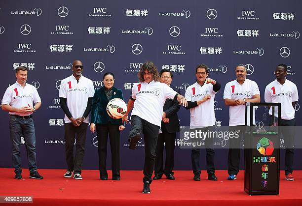Former Barcelona footballer Carles Puyol of Spain kicks a ball from the stage watched by Laureus World Sports Academy member Alexey Nemov Laureus...