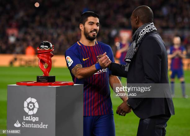 Former Barcelona French player Eric Abidal gives the Best Player of the Month award to Barcelona's Uruguayan forward Luis Suarez before the Spanish...