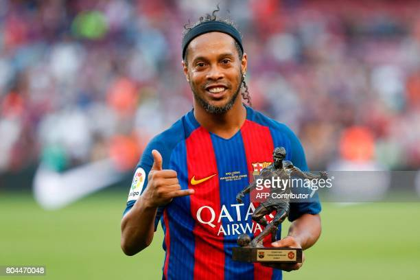 Former Barcelona's Brazilian forward Ronaldinho poses with the trophy for the best player after a charity football match between Barcelona Legends vs...