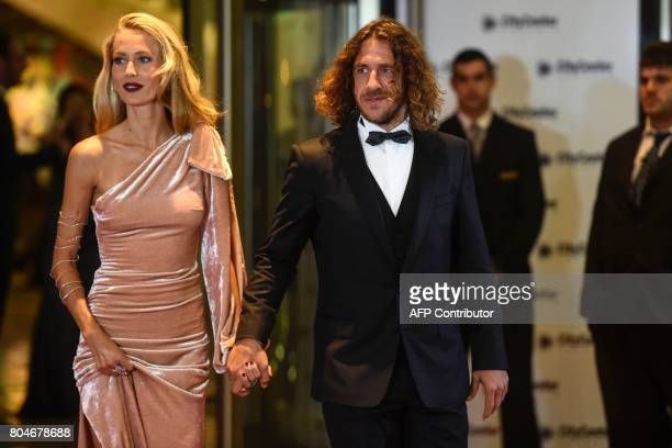 Former Barcelona's football player Carles Puyol and his wife pose on a red carpet upon arrival to attend Argentine football star Lionel Messi and...