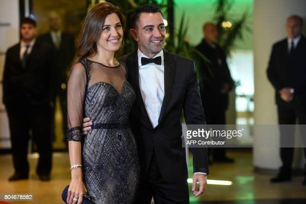 Former Barcelona's football player Xavi Hernandez and his wife pose on a red carpet upon arrival to attend Argentine football star Lionel Messi and...