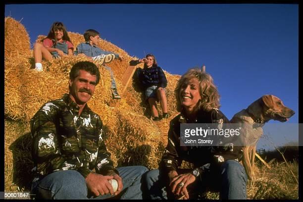 Former baseball AllStar Bill Buckner w wife Jody their children Christen Bobby Brittany sitting nr pet dog on haystack on ranch at home