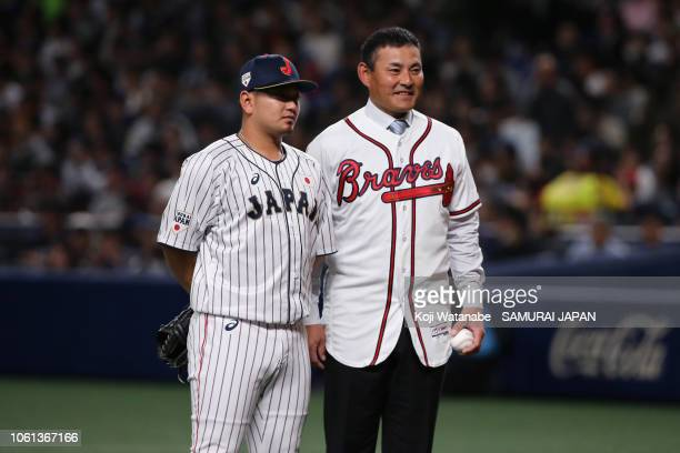 Former baseball player Kenshin Kawakami poses with catcher Tomoya Mori of Japan after throwing a ceremonial first pitch prior to the game five...